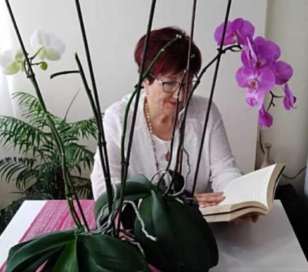 Imagen de la autora leyendo sentada a una mesa, tras una flores